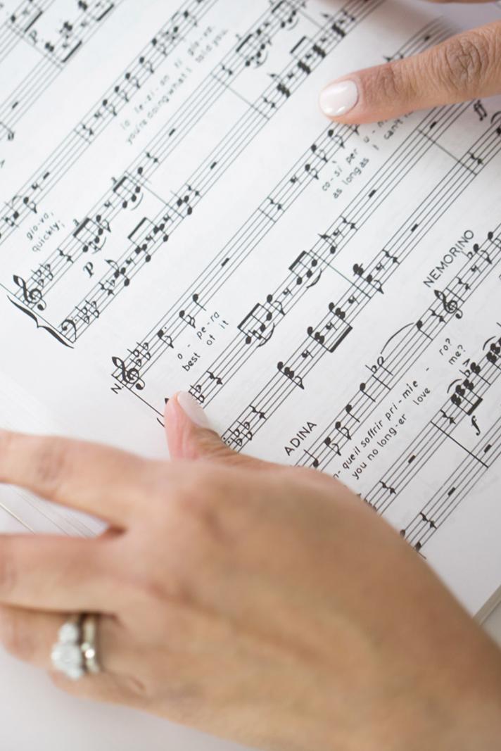 flipping through opera score - High Note Designs, LLC